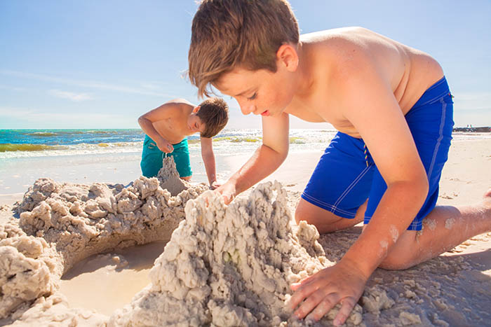kids playing making sand castles on the coast of mexico beach florida