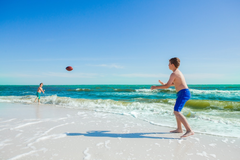 Boy playing catch on beach at Mexico Beach